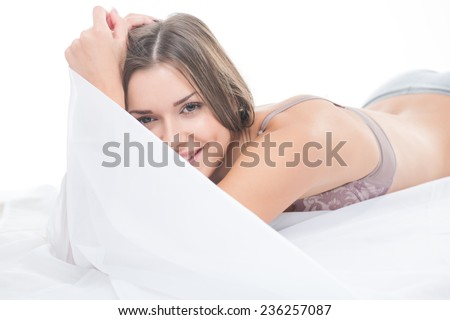 Half-length portrait of dark-haired beautiful smiling girl wearing sexy lingerie lying in the bed playing with the bedclothes thinking about her boyfriend - stock photo