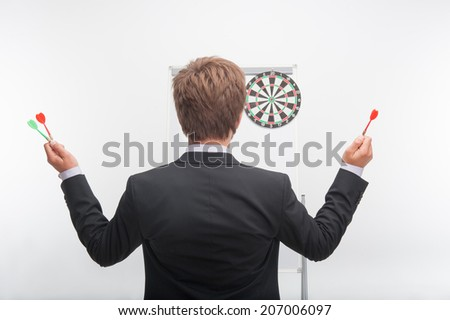 Half-length portrait of dark-haired man wearing black jacket standing back to us and holding darts in both his hands - stock photo