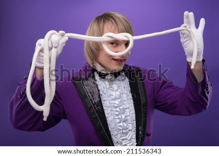 Half-length portrait of fair-haired matchless smiling juggler wearing splendid violet costume and white shirt making a knot using the white rope. Isolated on blue background - stock photo