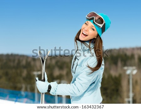 Half-length portrait of female downhill skier with skis in hands. Concept of winter sports and cute entertainment - stock photo