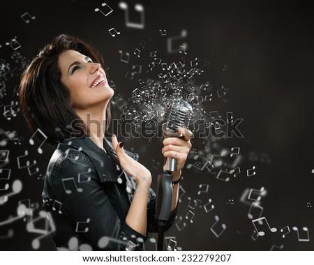 Half-length portrait of female rock musician keeping sounding mic on dark grey background - stock photo