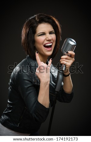 Half length portrait of female rock singer wearing black jacket and