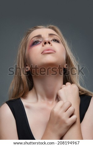 Half-length portrait of frightened young girl with black eye looking up and praying. Isolated on grey background - stock photo