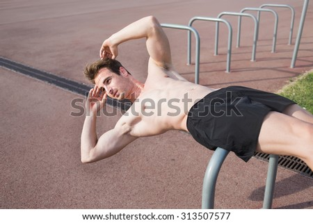 Half length portrait of handsome sportive man doing press abdominal exercise outdoors in summer sunny day, muscular build male runner warming up before began his morning run - stock photo