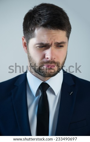 Half-length portrait of handsome young bearded grieved man wearing white shirt tie and blue jacket thinking about something. Isolated on white background - stock photo