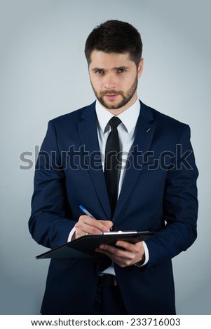 Half-length portrait of handsome young bearded man wearing white shirt tie and blue suit holding the black folder writing in it thinking about his decision. Isolated on white background - stock photo