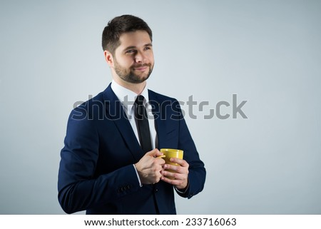 Half-length portrait of handsome young smiling man wearing white shirt tie and blue suit holding a yellow cup of coffee exulting in the morning. Isolated on white background - stock photo