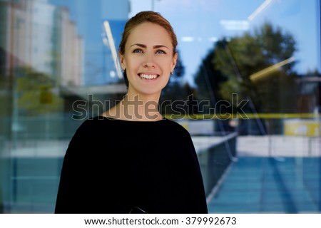 Half length portrait of happy and successful female hostess of modern hotel posing outside during work break, young cheerful businesswoman standing against office glass window with city reflection - stock photo