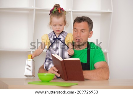 Half length portrait of happy funny handsome man and his cute little daughter wearing apron and preparing to cook with cooking book, grater and bowl, studio shot - stock photo