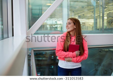Half length portrait of happy smiling college student with notepad in the hands resting after class in campus indoors, stylish young teenager girl after classes at school resting in hallway of college - stock photo