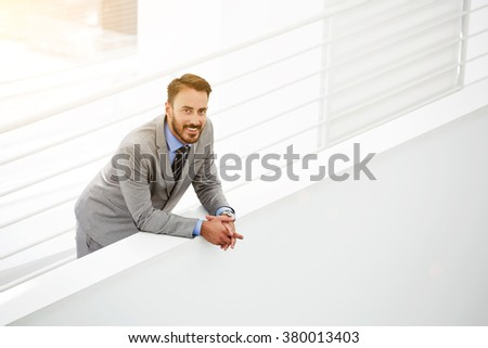 Half length portrait of happy young businessman in formal wear standing near copy space in modern interior, smiling bearded male manager resting in office hallway after successful meeting with clients - stock photo