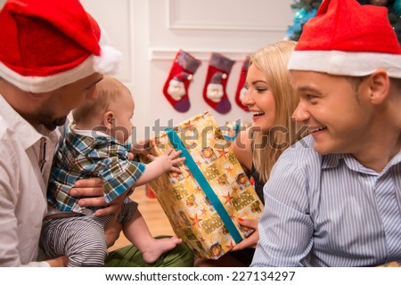 Half-length portrait of happy young family consisted of mom dad and little baby sitting with their friend on the floor near the Christmas tree unpacking presents celebrating the New Year holiday - stock photo