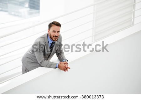 Half length portrait of intelligent male lawyer feeling happy after winning court case while standing in modern hallway, smiling young businessman dressed in classic suit resting after conference - stock photo