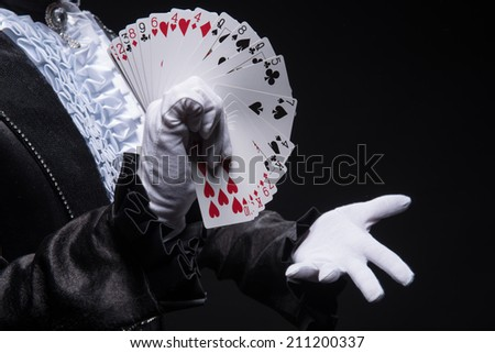 Half-length portrait of  juggler wearing interesting black costume and white shirt showing us his cards. Isolated on black background - stock photo