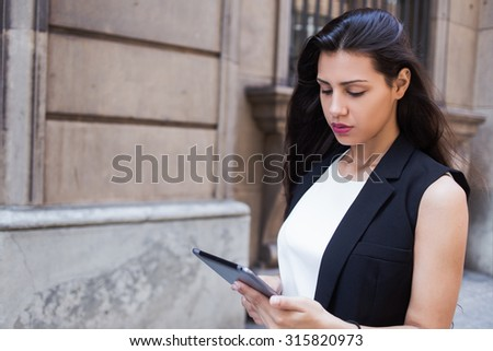 Half length portrait of latin business woman reading fashion news on her touch pad while walking on the street, modern female using digital tablet computer for navigation during walking in summer day - stock photo
