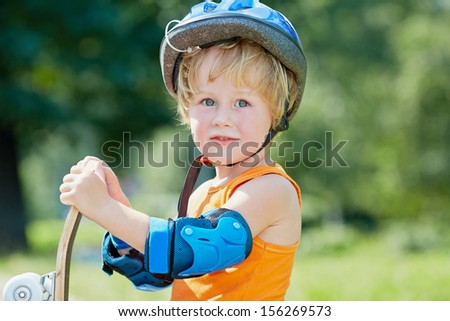 Half-length portrait of little boy who stands half-turned with skateboard in park - stock photo