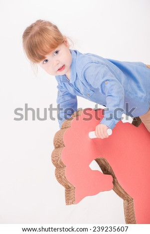 Half-length portrait of little lovely smiling girl wearing blue shirt and brown pants rocking on the pink wooden toy horse. Isolated on the white background - stock photo
