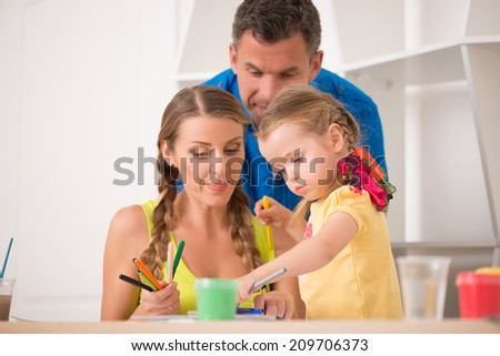 Half length portrait of lovely happy family drawing and painting at home together, father and mother showing their cute little daughter colorful  pens - stock photo