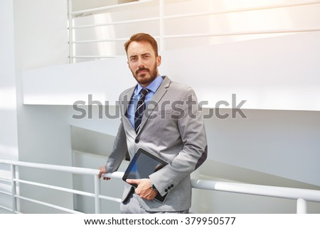 Half length portrait of man experienced engineer standing with touch pad in premises which he designed, male successful lawyer holding portable digital tablet while waiting start of the court hearing - stock photo