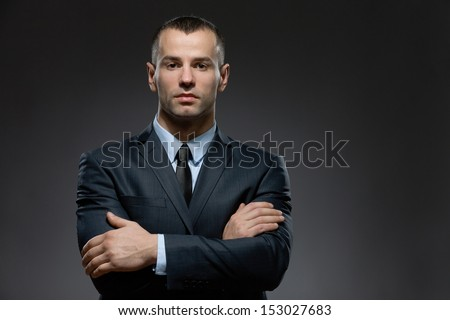 Half-length portrait of man wearing business suit and black tie with arms crossed - stock photo