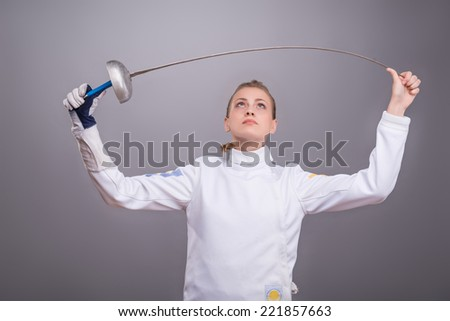 Half-length portrait of pretty girl wearing fencing costume checking her sword thinking about future competitions. Isolated on dark background - stock photo