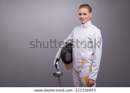 Half-length portrait of pretty smiling girl wearing fencing costume standing aside holding the rapier and fencing mask in one hand. Isolated on dark background - stock photo