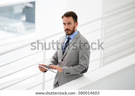 Half length portrait of rich businessman holding portable digital tablet during work break in hallway, confident young male financier count the costs via touch pad while standing in office interior - stock photo