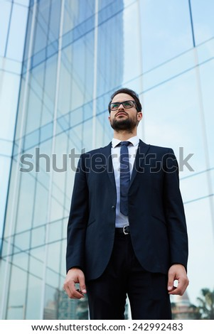 Half length portrait of serious handsome businessman at office building - stock photo