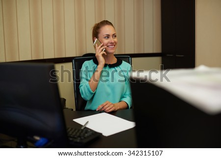 Half length portrait of smiling successful female entrepreneur sitting at her workplace and having telephone call, young pretty businesswoman working in office interior while using digital devices  - stock photo