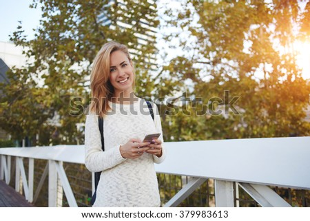Half length portrait of smiling woman with mobile phone posing while standing on bridge in spring day, cheerful female tourist waiting for call on cell telephone during walking in unfamiliar city - stock photo