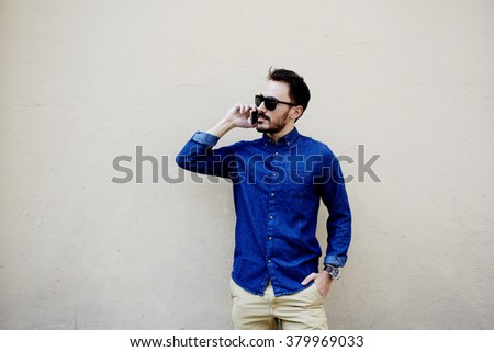 Half length portrait of stylish hipster guy talk with friend via mobile smart phone while strolling outdoors,bearded man calling with cell phone while standing against street wall with copy space area - stock photo
