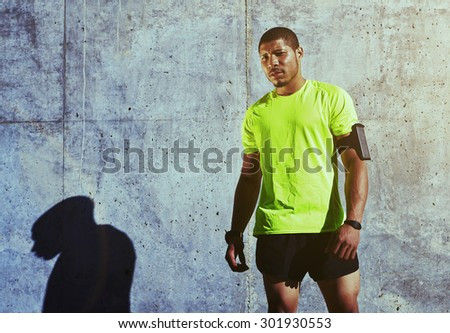 Half length portrait of sweaty man athlete resting after physical exercise while standing against cement wall background with copy space area for your text message or advertising, runner having a rest - stock photo