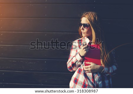 Half length portrait of teenager girl with book in the hands standing against wooden wall with copy space area for your advertising content, female student in sunglasses at university campus - stock photo
