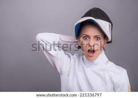 Half-length portrait of the fair-haired astonished girl wearing white fencing costume holding at her fencing mask. Isolated on grey background - stock photo