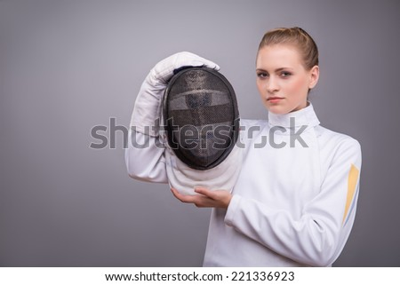 Half-length portrait of the fair-haired girl wearing white fencing costume standing aside showing us her fencing mask looking at us with surprise. Isolated on grey background - stock photo