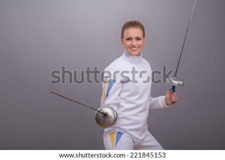 Half-length portrait of the fair-haired pretty serious girl wearing white fencing costume standing holding two swords prepared for duel. Isolated on grey background - stock photo