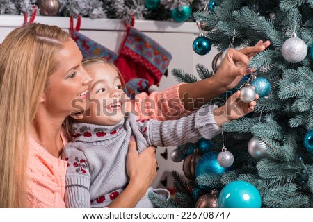 Half-length portrait of the little cute fair-haired smiling girl with her lovely mom wearing warm sweaters and jeans sitting aside near the Christmas tree decorating it - stock photo