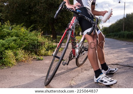 Half-length portrait of the man wearing sport uniform and sunglasses riding a great bike in the park preparing for the competition stopped on the road to drink some water - stock photo