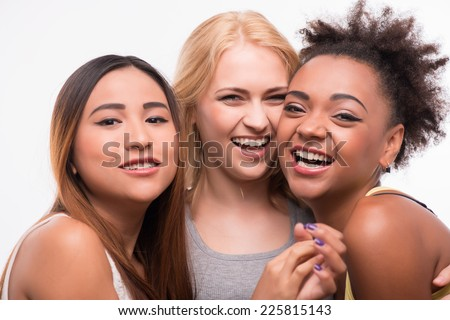 Half-length portrait of three beautiful smiling girls looking at us. Isolated on white background - stock photo