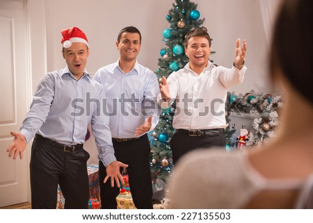 Half-length portrait of three happy men wearing white shirts and black pants greeting guests on their great party celebrating the New Year - stock photo