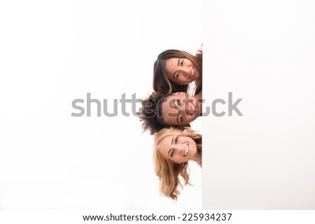 Half-length portrait of three young lovely smiling girls looking out of the big white poster for copy place. Isolated on white background - stock photo