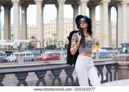 Half length portrait of trendy and attractive model posing on the background of ancient urban building and having a good time, beautiful Caucasian woman is enjoying her weekends in Saint Petersburg  - stock photo