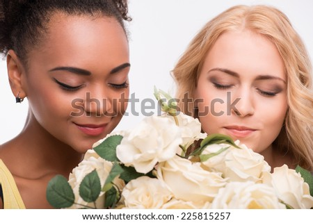 Half-length portrait of two young pretty smiling women wearing colorful T-shirts standing with the bouquet of white roses smelling the aroma of it. Isolated on white background - stock photo