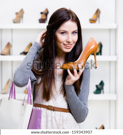 Half-length portrait of woman handing brown leather heeled shoe in shopping center - stock photo