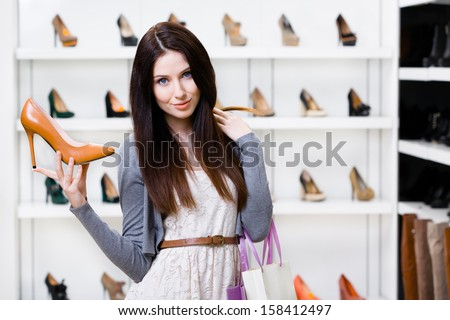 Half-length portrait of woman keeping brown leather stylish pump in shopping center - stock photo
