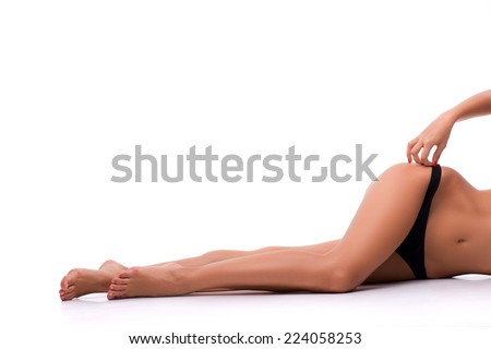 Half-length portrait of woman wearing black lingerie lying aside to us showing her ideal figure isolated on white background - stock photo