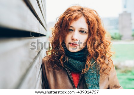 Half length portrait of young beautiful caucasian redhead woman looking in camera, pensive - intense, thoughtful, determination concept - stock photo