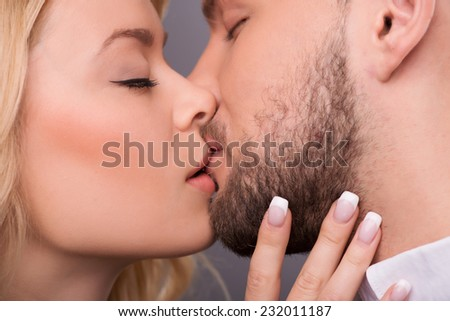 Half-length portrait of young beautiful couple standing with closed eyes facing each other kissing. Isolated on dark background - stock photo