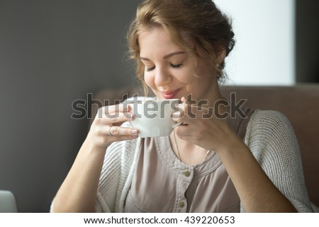 Half-length portrait of young beautiful female sitting at coffee shop with cup of tea or cappuccino. Woman enjoying hot drink in the morning. Attractive model sipping coffee with closed eyes - stock photo