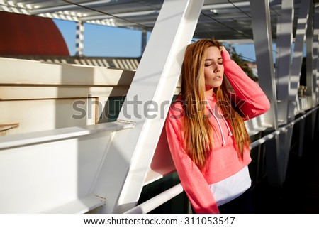 Half length portrait of young beautiful woman relaxing outdoors while enjoying the sun with closed eyes, stylish hipster girl resting after walk during her free recreation time,female relaxing outside - stock photo